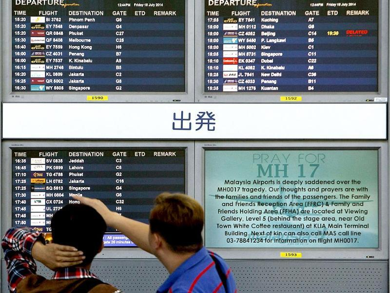Bystanders look at a board displaying flight information and a