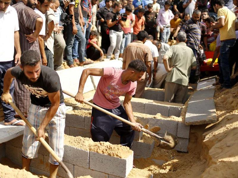 Palestinians prepare the graves for eight members from Abu Jarad family, including three children, who medics said were killed by an Israeli tank shell, at a cemetery in Beit Lahiya in the northern Gaza Strip (Reuters)