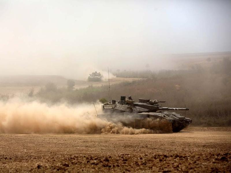 Israeli Merkava tanks roll towards the Israeli-Gaza border in an army deployment area. (AFP Photo)