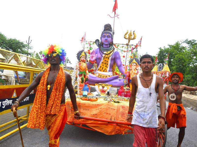 Kanwarias or devotees of Shiva pick up their Ganga water carriers at NH 58 in Ghaziabad. (HT Photo/Sakib Ali)