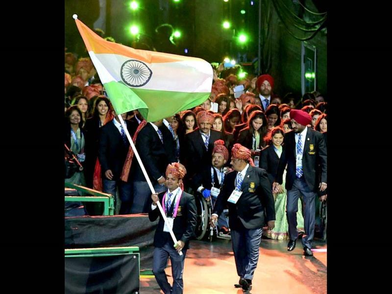 Ace shooter Vijay Kumar holds the Tricolour as he leads the Indian contingent. (PTI Photo)