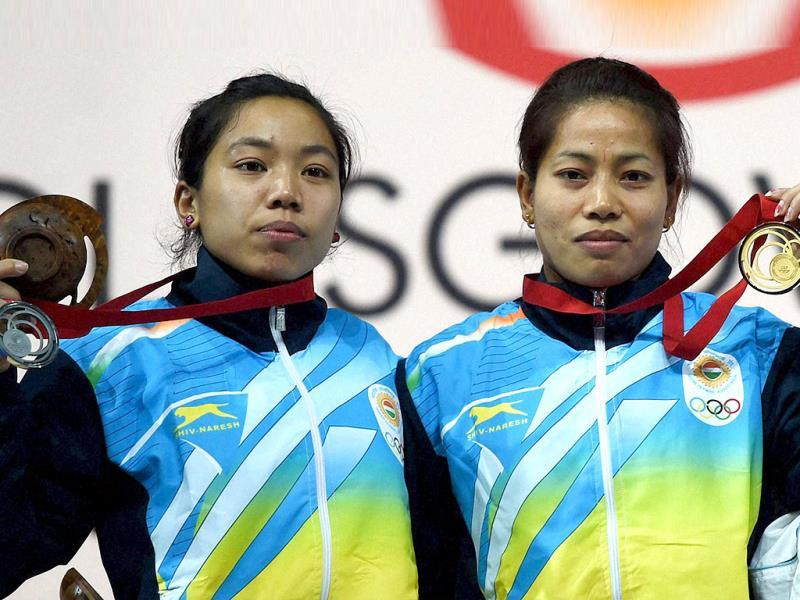 India's gold medalist Sanjita Khumukcham and compatriot silver medalist Chanu Saikhom during the medal presentation ceremony of 48-kg women's weightlifting event (PTI Photo)