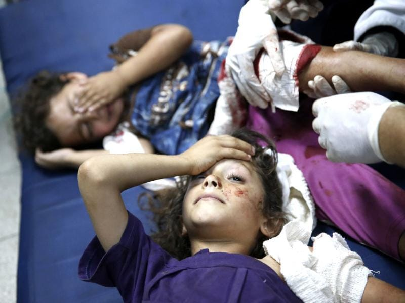 Palestinian children, wounded in an Israeli strike on a compound housing a UN school in Beit Hanoun, in the northern Gaza Strip, are treated as they lay on the floor at the emergency room of the Kamal Adwan hospital in Beit Lahiya. (AP photo)