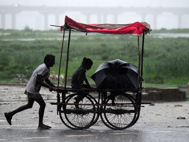 India, Allahabad: An Indian man pushes his trolley during heavy rain in Allahabad on July 19, 2014. (AFP/Sanjay Kanojia)