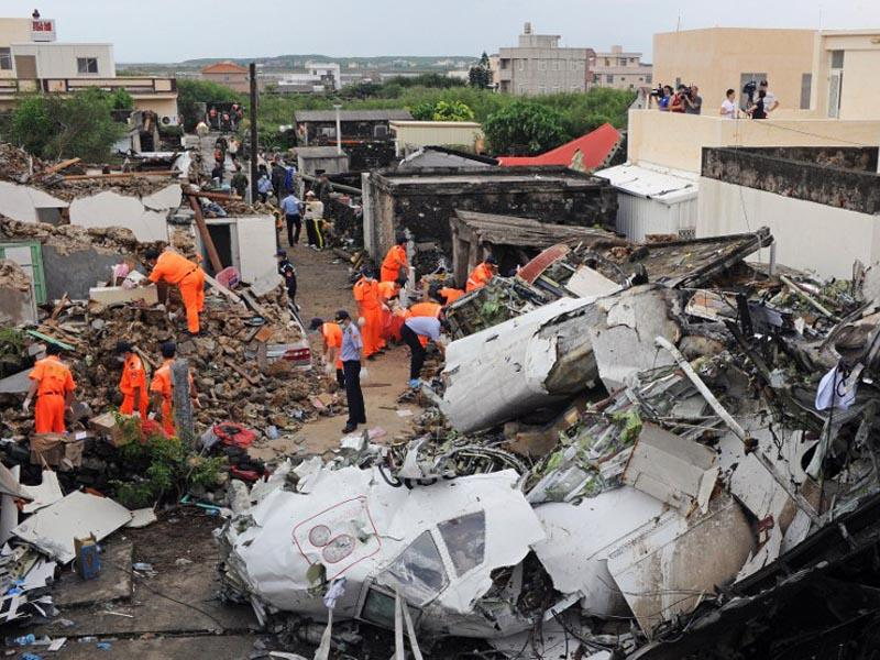 Taiwan, Magong:  Rescue workers and firefighters search through the wreckage where TransAsia Airways flight GE222 crashed the night before near the airport at Magong on the Penghu island chain on July 24, 2014. (AFP/Sam Yeh)