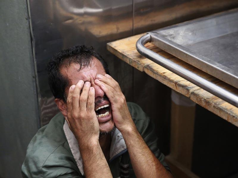 Gaza, Beit Lahiya:  A Palestinian man cries after identifying the body of his loved one, killed in an Israeli strike, inside the morgue of Kamal Adwan hospital in Beit Lahiya, northern Gaza Strip on July 24, 2014. (AP/Lefteris Pitarakis)