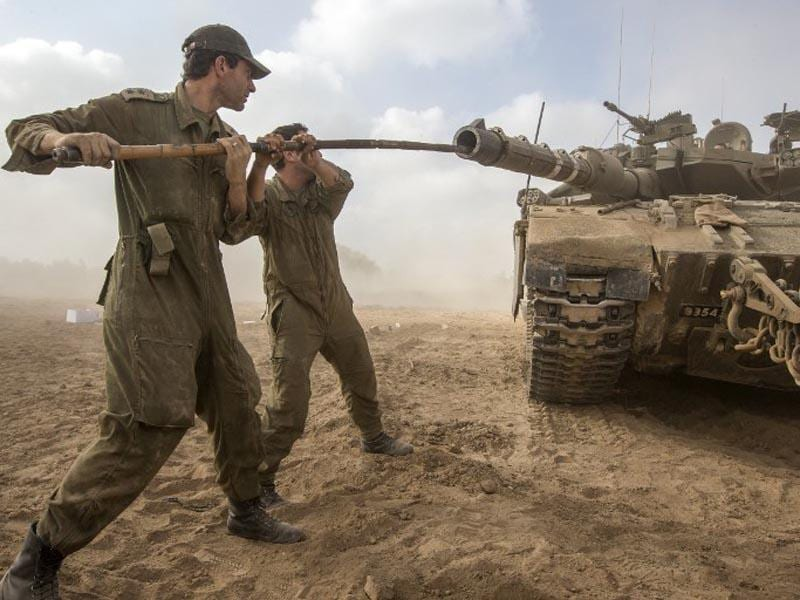 Israel, Israel-Gaza Border:  Israeli soldiers work on their Merkava tank at an army deployment area near Israel's border with the Gaza Strip, on July 24, 2014. (AFP/Jack Guez)