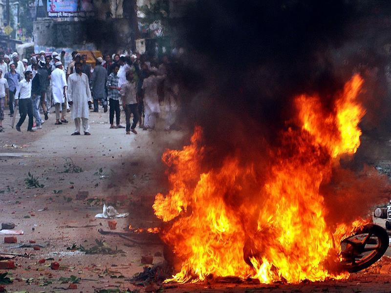 People stand near a burning motorcycle, set on fire during a protest between two communities in Saharanpur district of Uttar Pradesh. Officials say a land dispute triggered the violent clash that left three people dead and a dozen injured. (AP photo)