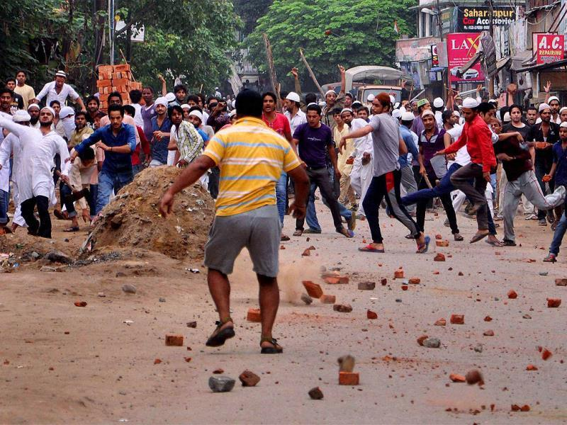 Stone pelters in action during violent clashes between two communities over a land dispute in Saharanpur. (PTI photo)