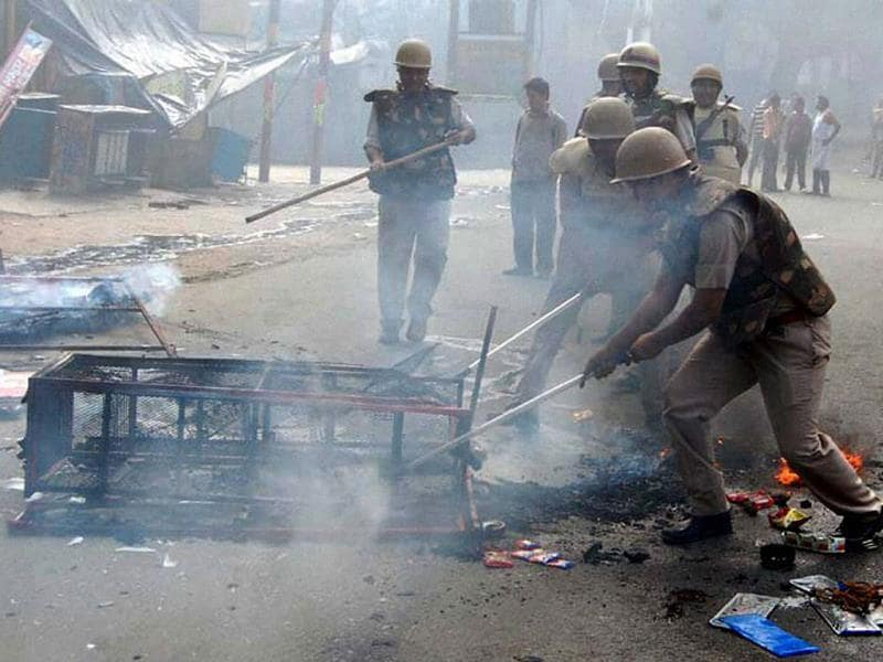 Policemen douse the fire at a rack after violent clashes broke out between two communities over a land dispute in Saharanpur. (PTI photo)