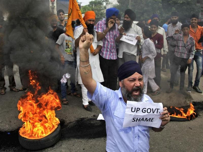 A man shouts slogans as a small group of Sikhs burn tires to block traffic during a protest against the Uttar Pradesh state government in Jammu. (AP Photo/Channi Anand)