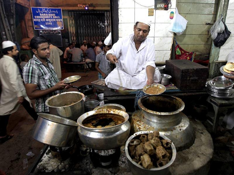 A vendor dishes out Ramzan delicacies near Jama Masjid between Iftar and Sehri at old Delhi. (HT Photo/Ajay Aggrwal)