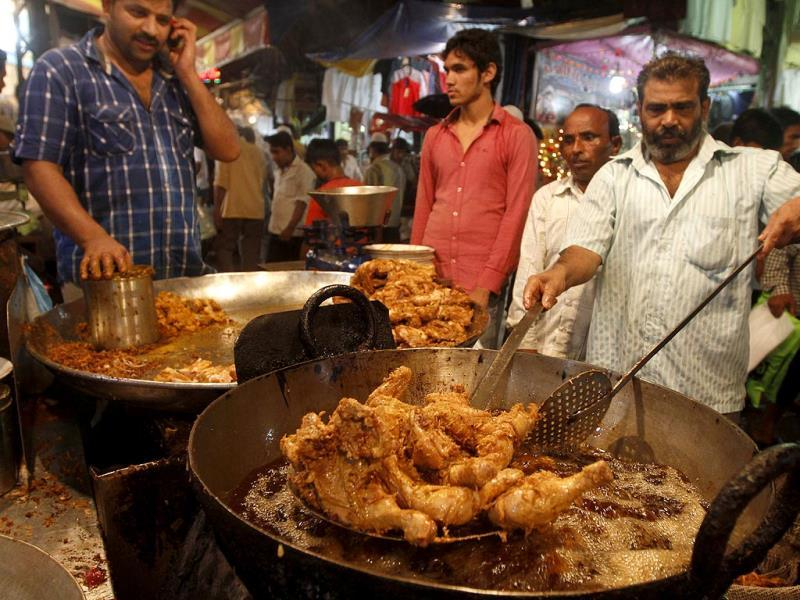 Workers cook a non-vegetarian food on eve of Eid at Jama Masjid area market, in New Delhi. (HT photo/Sanjeev Verma)