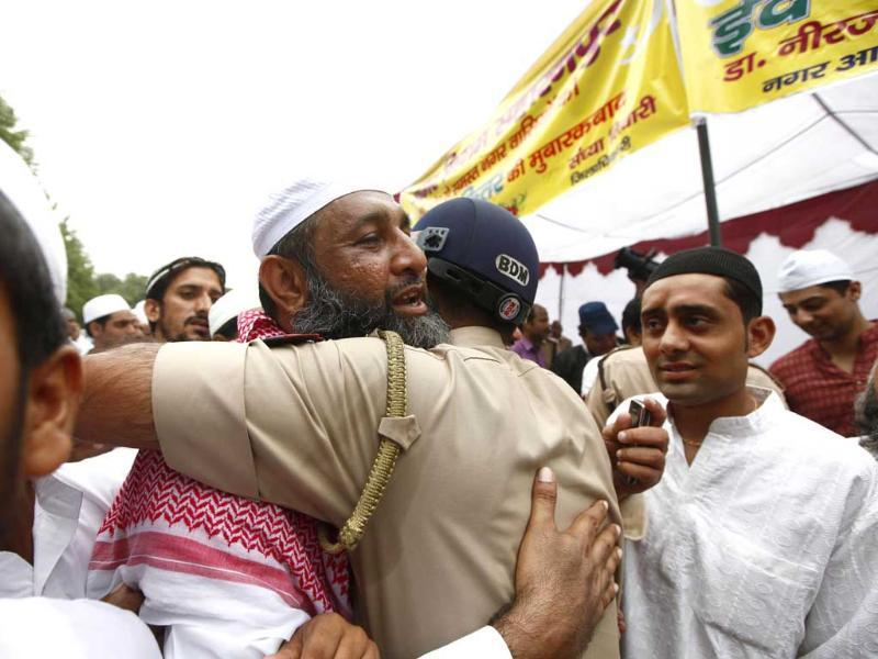 A man hugs a police official after offering prayers during the fastival of Eid al-fitr, marking the end of Ramzan in Saharanpur. (Virendra Singh Gosain/HT photo)
