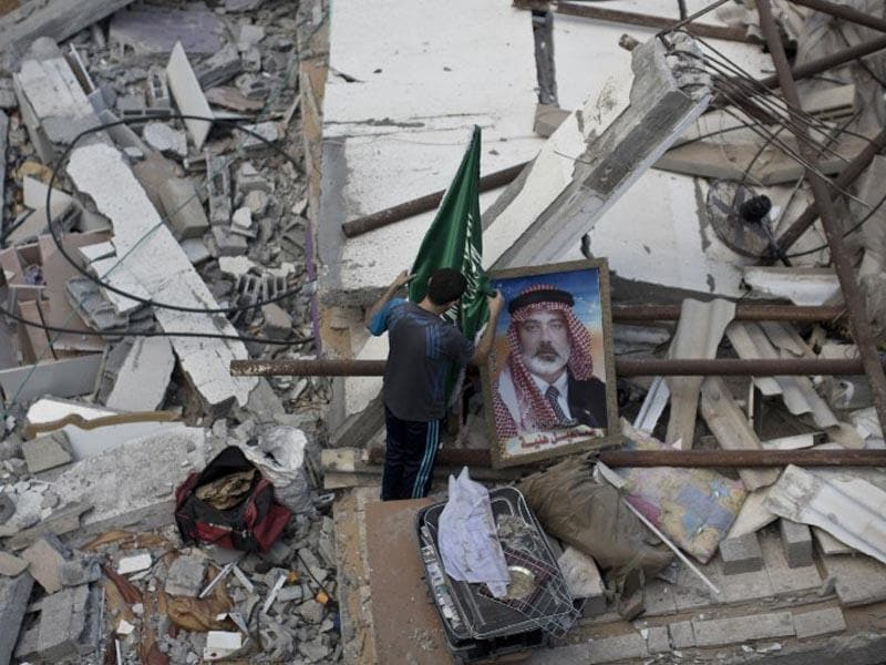 A Palestinian man displays an Islamist Hamas movement flag and a portrait of Hamas top leader in Gaza, Ismail Haniya, on the rubble of the latter's house after it was hit by an overnight Israeli air strike on July 29, 2014 in Gaza City. (AFP/Mahmud Hams)