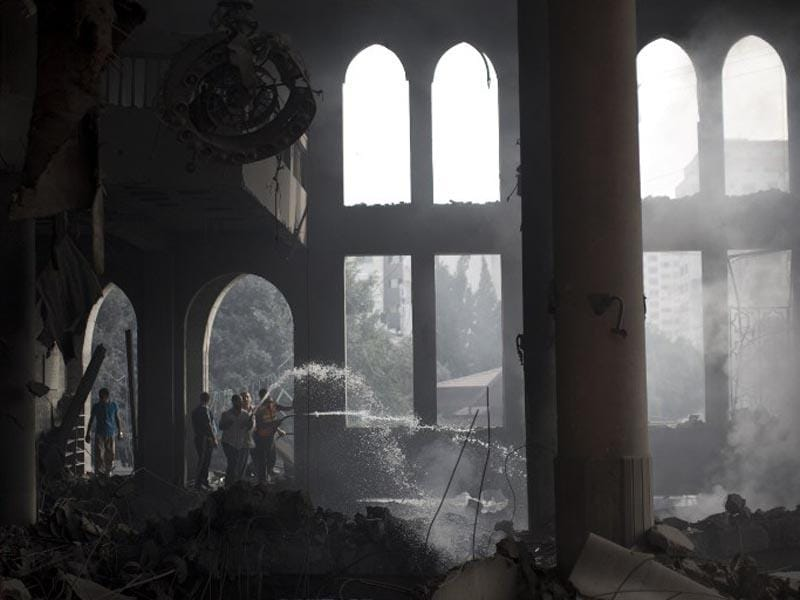 Palestinian firefighters extinguish fire at a mosque after it was hit by an Israeli air strike on July 29, 2014, in Gaza City. (AFP/Mahmud Hams)