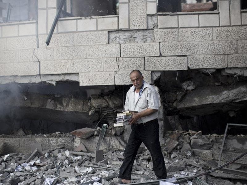A Palestinian man holds copies of the Koran, Islam's holy book, as he inspects the rubble of a destroyed mosque hit by an Israeli air strike on July 29, 2014, in Gaza City. (AFP/Mahmud Hams)