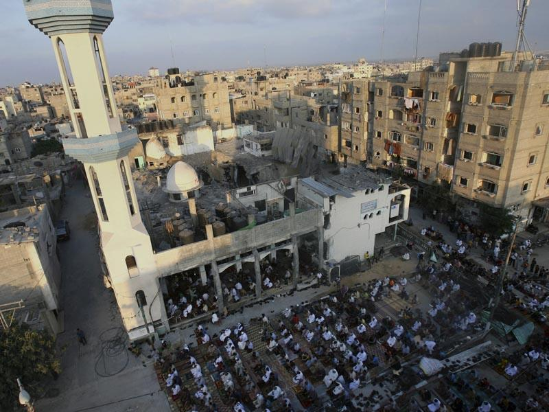 Palestinians pray early morning prayer during the first day of Eid al-Fitr at the destroyed Al Farouk mosque on July 28, 2014. As Muslims began celebrating on Monday, there was mostly fear and mourning instead of holiday cheer in the Gaza Strip. (AP/Eyad Baba)
