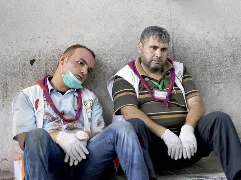 Exhausted Palestinian medics take a break after carrying wounded people injured from an Israeli strike in Shijaiyah neighborhood, into the emergency room at Gaza City's Shifa hospital. (AP Photo)