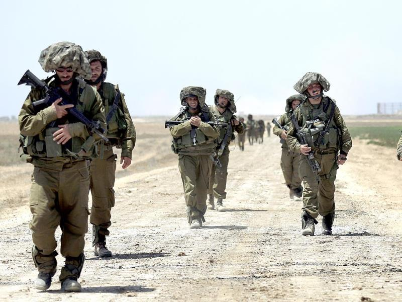 Israeli reserve soldiers return to Israel after fighting in Khan Younis in the Gaza Strip, while walking on a road near the Israel Gaza border. (AP Photo)