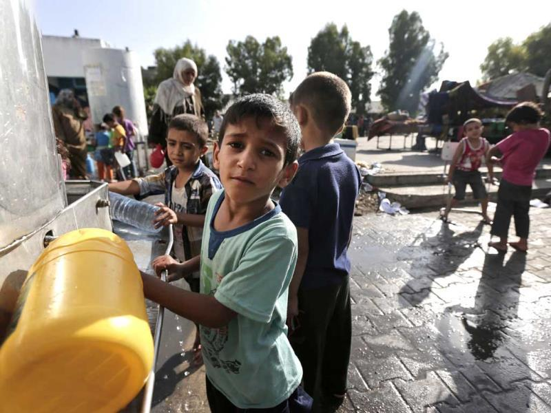 Displaced Palestinian children collect water, at the Abu Hussein UN school, in Jebaliya refugee camp, northern Gaza Strip. (AP Photo)