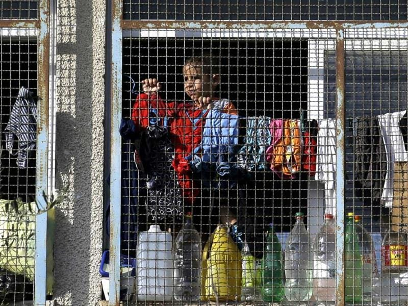 A displaced Palestinian child watches the passing traffic from inside a classroom at the Abu Hussein UN school, in Jebaliya refugee camp, northern Gaza Strip. (AP Photo)
