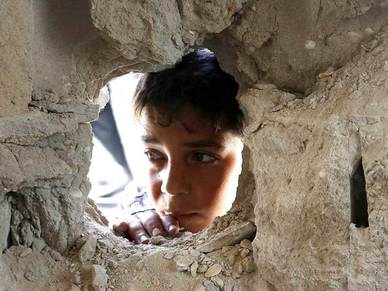 A boy looks through a hole in the wall made by the shelling at the Abu Hussein UN school in the Jebaliya refugee camp in the northern Gaza Strip. (AP Photo)