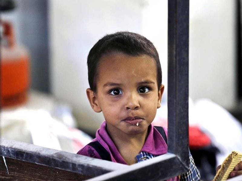 A Palestinian boy eats a snack inside a classroom at the Abu Hussein UN school in Jebaliya refugee camp, northern Gaza Strip. The school was hit by a series of Israeli artillery shells. (AP Photo)
