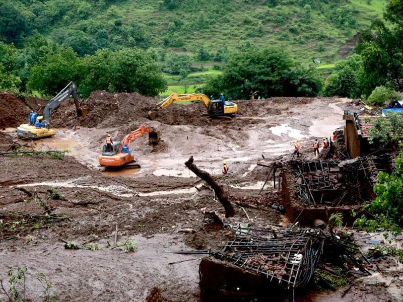 Earthmovers clear mud and slush at the site of a landslide in Malin village, in Maharashtra. (AP Photo)