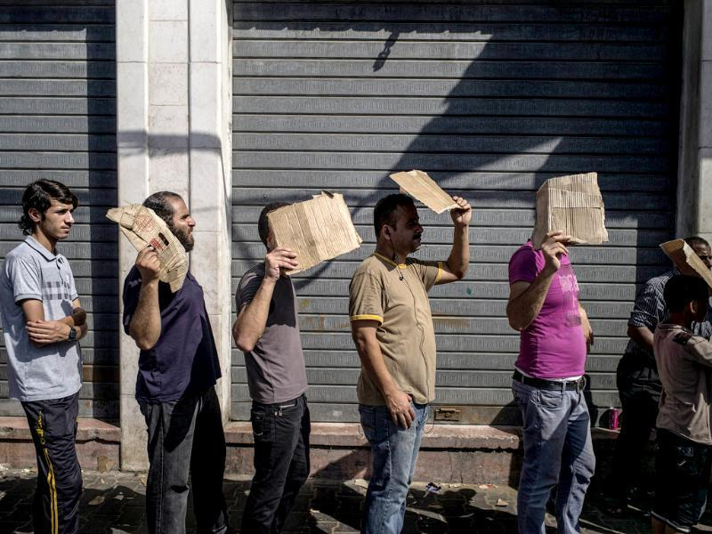 Palestinian men hold up pieces of cardboard to protect themselves from the sun as they queue up for bread in the central avenue of Gaza City. (AFP photo)