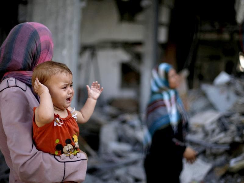 A Palestinian woman holds her daughter as she looks at the wreckage of her house in Beit Hanoun town, which witnesses said was heavily hit by Israeli shelling and air strikes during Israeli offensive, in the northern Gaza Strip. (Reuters photo)