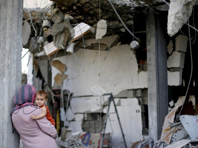A Palestinian woman holds her daughter as she looks at the wreckage of her house in Beit Hanoun town, which witnesses said was heavily hit by Israeli shelling and air strikes during an Israeli offensive, in the northern Gaza Strip. (Reuters photo)