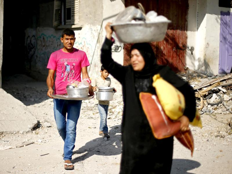 Palestinians carry belongings from their damaged house in Beit Hanoun town, which witnesses said was heavily hit by Israeli shelling and air strikes during Israeli offensive, in the northern Gaza Strip. (Reuters photo)