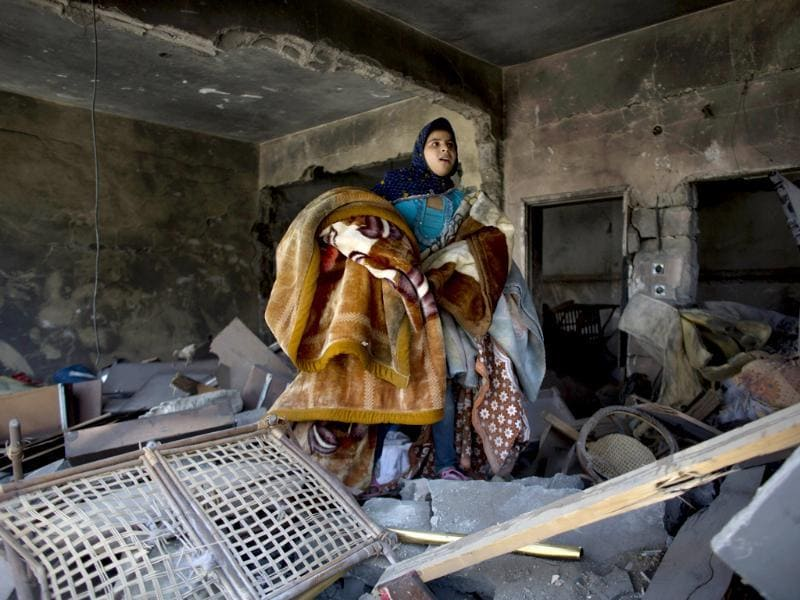 A Palestinian girl salvages blankets from a destroyed house in the heavily bombed Gaza City neighborhood of Shijaiyah, close to the Israeli border. (AP photo)