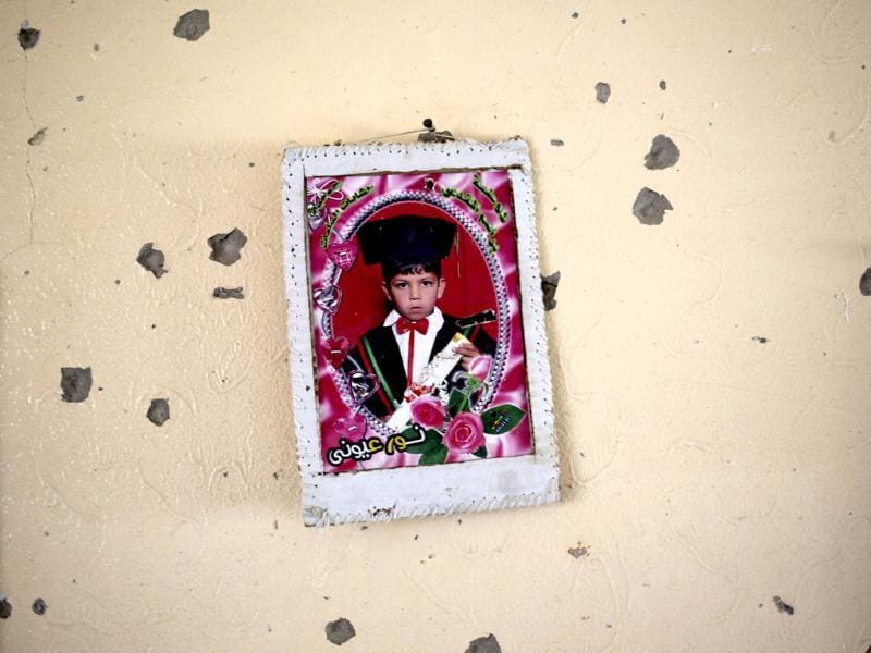 A graduation photo of a Palestinian boy is hung on the wall in a destroyed house in the heavily bombed Gaza City neighborhood of Shijaiyah, close to the Israeli border. (AP photo)