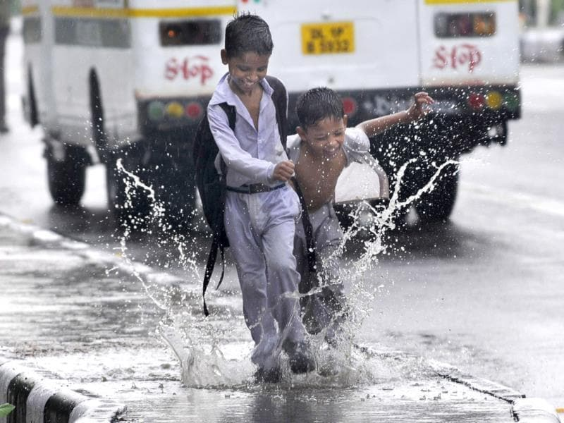 Students enjoy the rains in Noida. (Sunil Ghosh/HT photo)