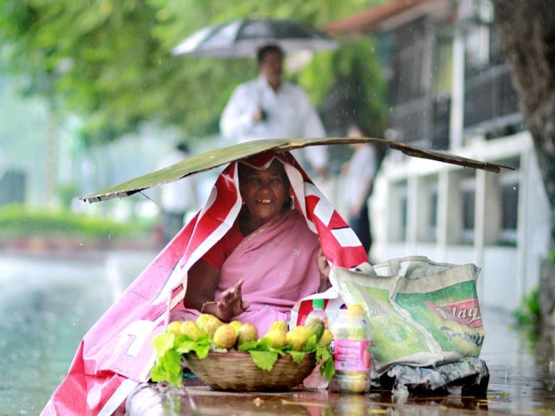A woman protects herself during rain at Mandi House in New Delhi. (Arun Sharma/HT photo)