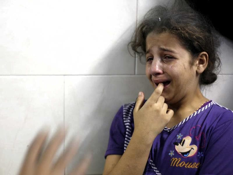 A Palestinian girl cries, as her father (unseen), wounded in an Israeli air strike on the al-Shati refugee camp, is treated at the al-Shefa hospital in Gaza City. (AFP Photo)