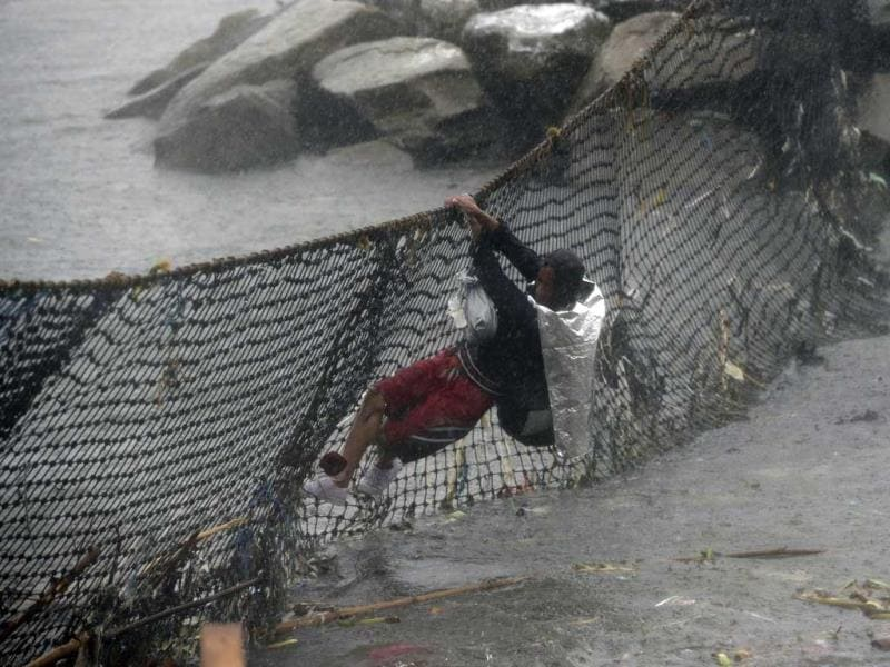 A Filipino man hangs on a net to cross waters as he moves to safer grounds during heavy rainfall at Manila's bay, Philippines. (AP Photo)