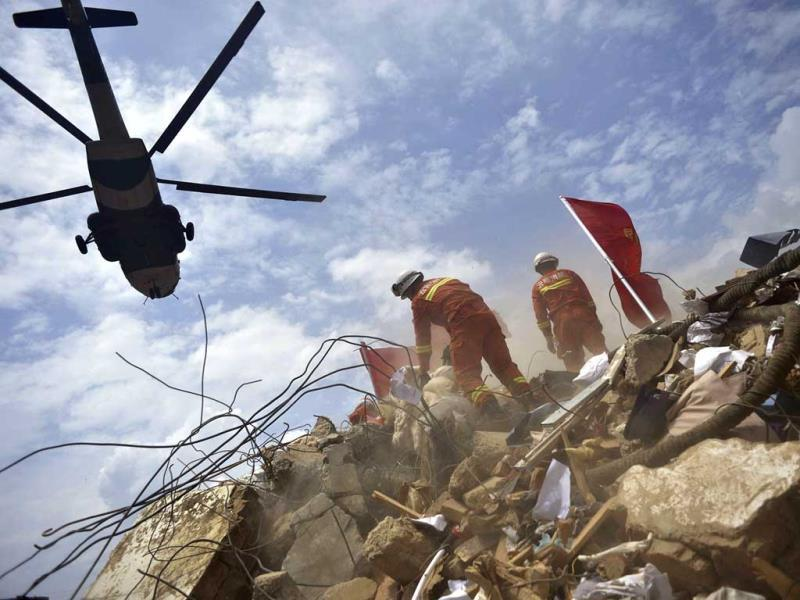 A helicopter flies over rescue workers at the epicenter of an earthquake that struck the town of Longtoushan in Ludian county in southwest China's Yunnan province. (AP Photo)