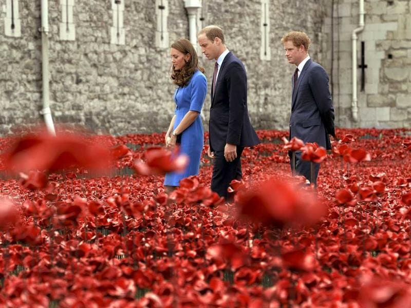 Kate, the Duchess of Cambridge, her husband Britain's Prince William, the Duke of Cambridge, and his brother Prince Harry visit Paul Cummins' art installation entitled 'Blood Swept Lands and Seas of Red' for its official unveiling in the dry moat of the Tower of London. (AP Photo)