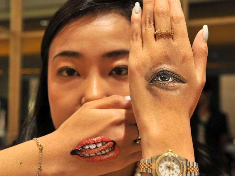 A woman displays body-paintings of her eye and her mouth on the back of her hands after Japanese body-painting artist Hikaru Cho (unseen in this picture) painted at an art event called