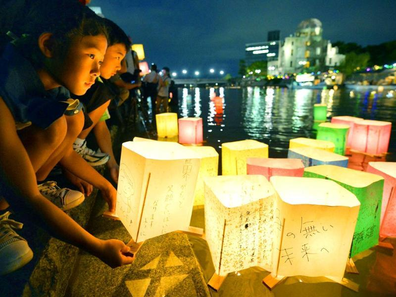A girl prepares to release paper lanterns with a message for peace on it in the Motoyasu River near the Atomic Bomb Dome in Hiroshima, western Japan. (AP Photo)