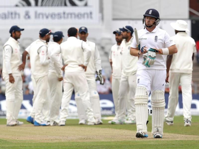 England's Ian Bell leaves the pitch after being caught out by India captain Mahendra Singh Dhoni (AFP Photo)