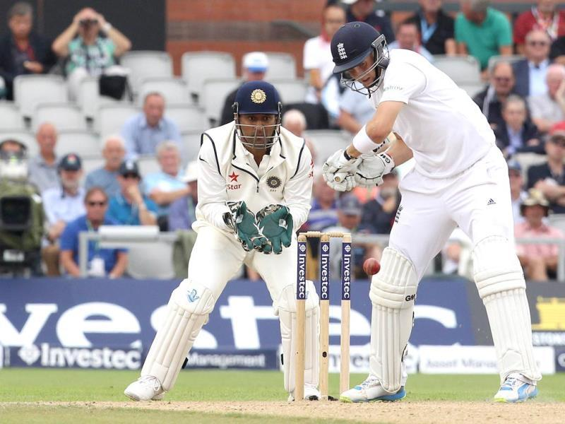 India captain Mahendra Singh Dhoni looks on as England's Joe Root plays a shot (AFP Photo)