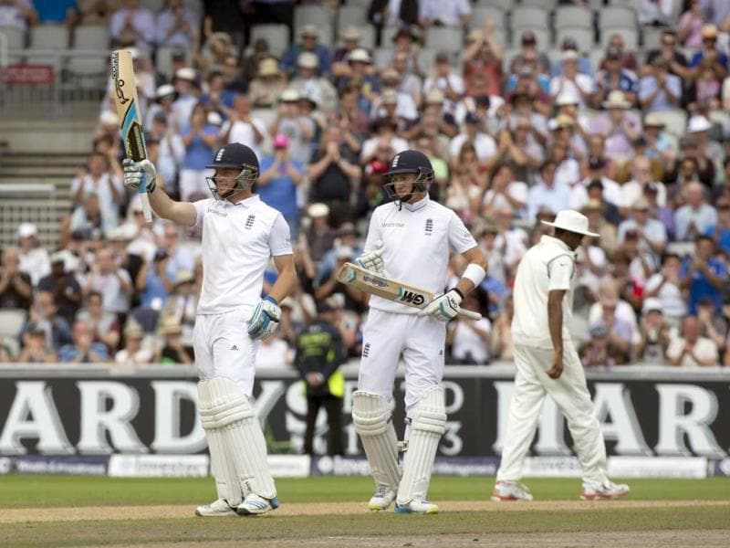 As teammate Joe Root (C) looks on, England's Jos Buttler (L) raises his bat as he reaches 50 on the third day of the fourth Test against India at Old Trafford cricket ground, in Manchester. (AP Photo)