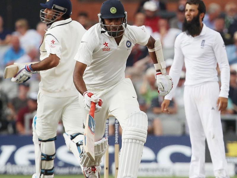 Ravichandran Ashwin (C) completes a run with captain MS Dhoni (L) during the third day of the fourth Test between England and India at Old Trafford in Manchester. (AFP Photo)