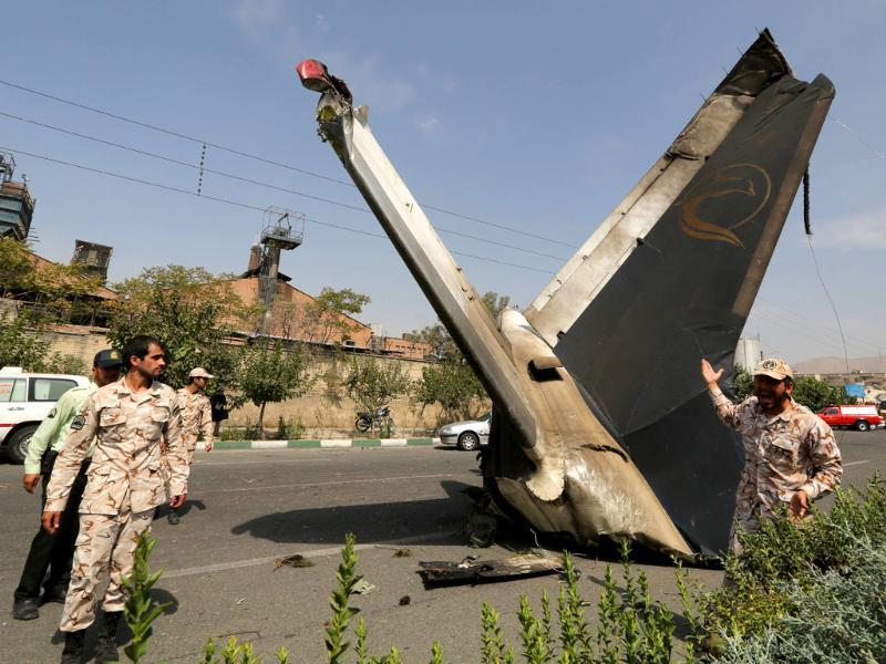 A member of the Iranian Revolutionary Guards reacts as he stands next to the remains of a plane that crashed near Tehran's Mehrabad airport. (AFP photo)