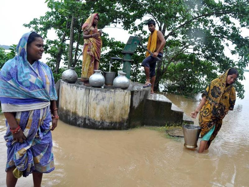 A woman wades through flood water as she carries drinking water collected from a handpump in Batira village, Kendrapada district. (Arabinda Mahapatra/HT Photo)