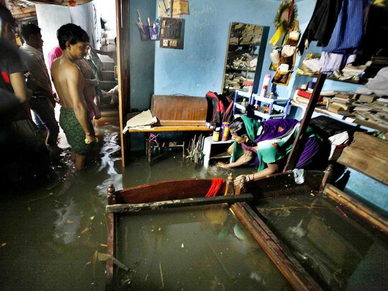 A woman tries to drain out the water flooded in her house in Pandia Kera village of Puri, in Odisha. (Raj K Raj/HT Photo)